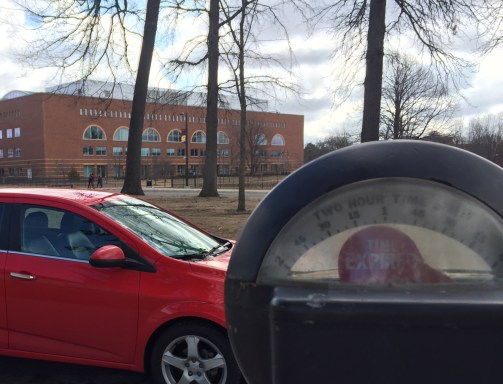 An expired meter outside of the University Center has a ticket-less car in its spot.