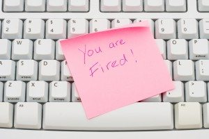 A pink sticky note sitting on a computer keyboard,You are fired