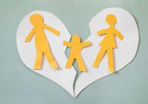 Paper cutout family split apart on a paper heart - divorce concept