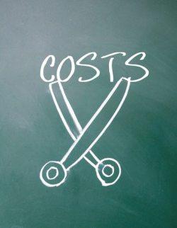 abstract scissors cut costs symbol on blackboard