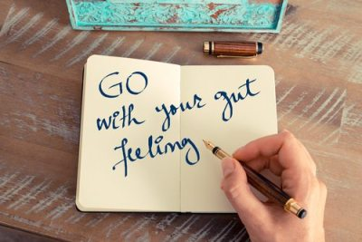Retro effect and toned image of a woman hand writing a note with a fountain pen on a notebook. Motivational concept with handwritten text GO WITH YOUR GUT FEELING
