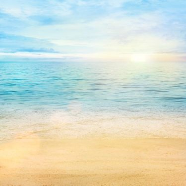 Beautiful sea background. Golden sand with blue ocean and cloudscape in the back.