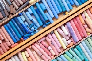 Set of multicolored pastel crayons in wooden artist box closeup, top view