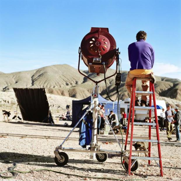 Film crew in desert, spotlight in foreground