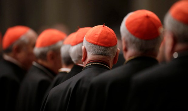 Cardinals attend a prayer at Saint Peter's Basilica in the Vatican March 6, 2013. Catholic cardinals said on Tuesday they wanted time to get to know each before choosing the next pope and meanwhile would seek more information on a secret report on alleged corruption in the Vatican. REUTERS/Max Rossi (ITALY - Tags: RELIGION)