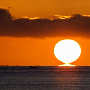 Golden sunrise over the sea with a fishing boat