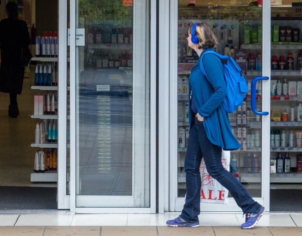 Consumerism - woman walking past a shop