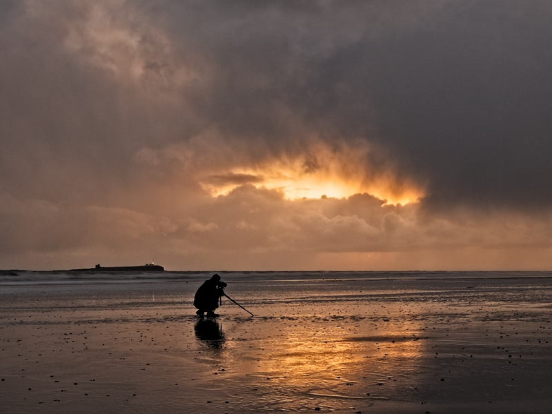 Reliable ancillary equipment like a tripod is essential. Man on beach shooting the sunrise.