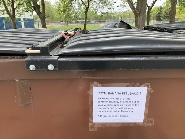 Photo of a garbage dumpster with a sign taped to it.