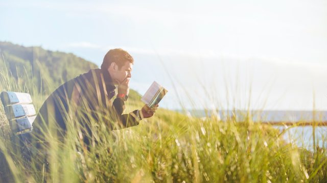 Photo of an introvert reading near a lake.