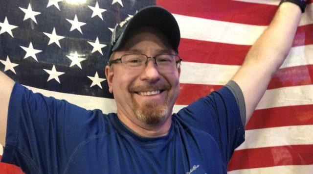 Picture of Martin C. Fredricks IV holding a USA flag.