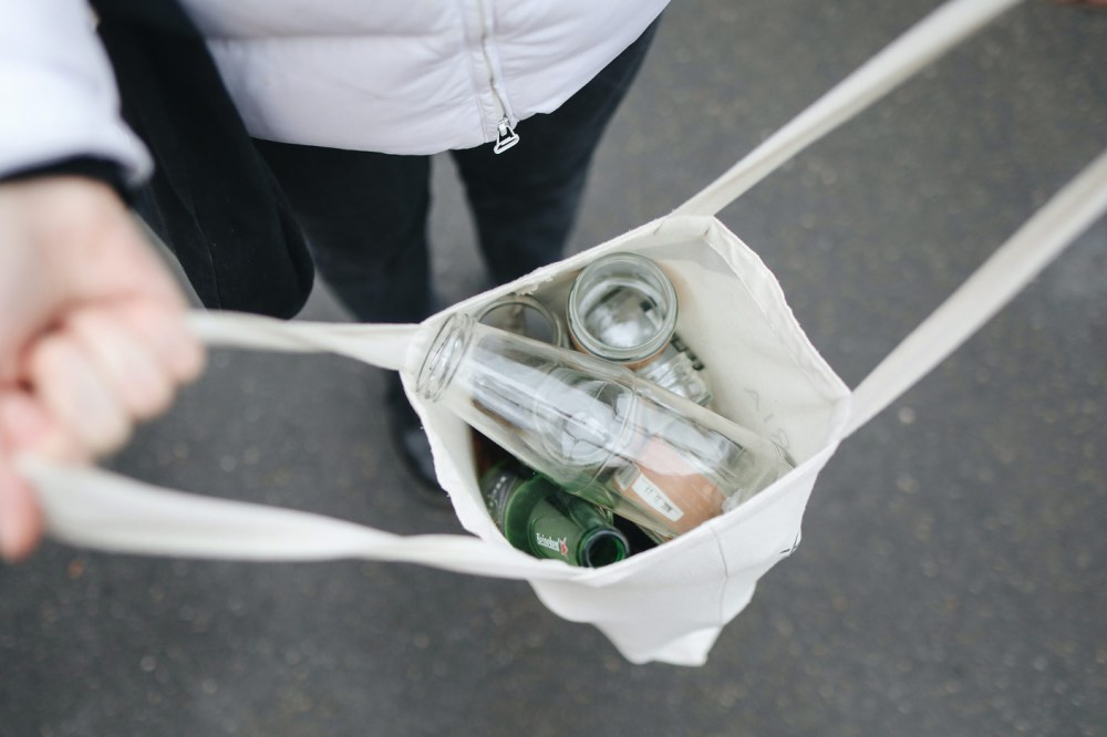 The picture represents a man holding a reusable bag filled with bottles ready for recycling.