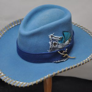 Baby blue drover hat with denim pockets, thick dark blue hatband and blue feathers