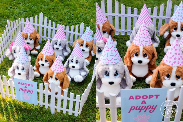 "Plush puppies wearing party hats, in a pen with a sign that says ""Adopt a Puppy""."