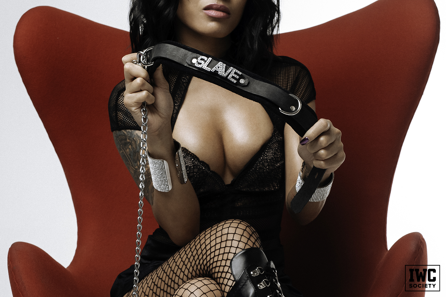 asian dominatrix Asia Perez holding a black collar that says slave in rhinestones