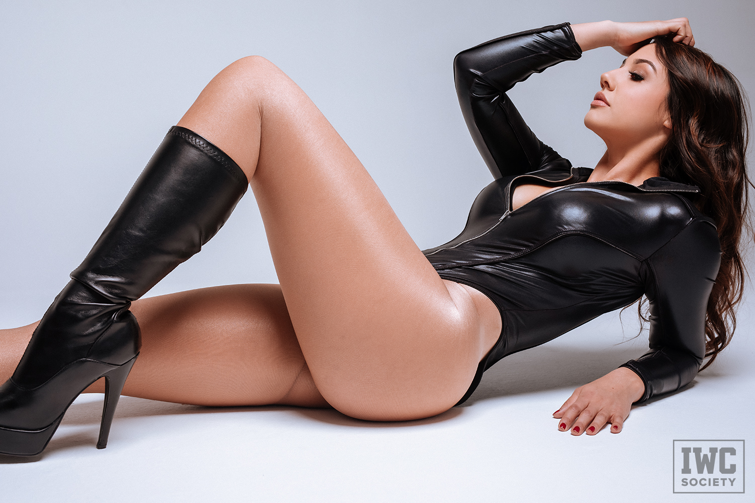 financial dominatrix lounging in black wet look bodysuit