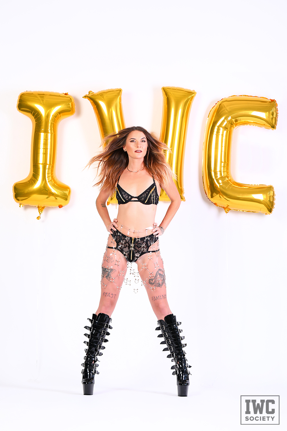 Financial dominatrix Goddess Emerald posing in black lingerie and black boots in front of gold IWC letters for iWantClips