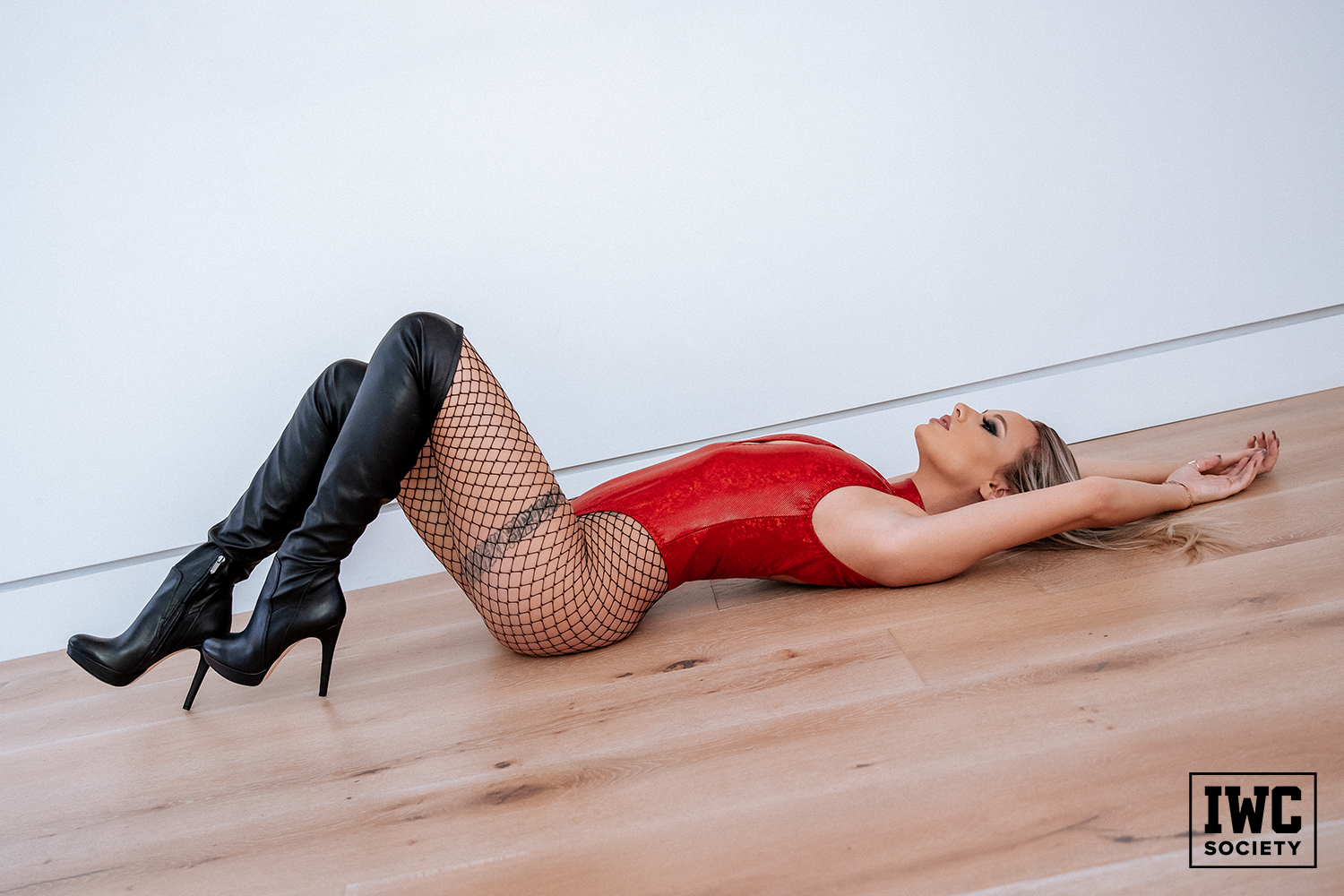 spoiled domme laying down and showing off her curvy body in a shiny metallic red bodysuit