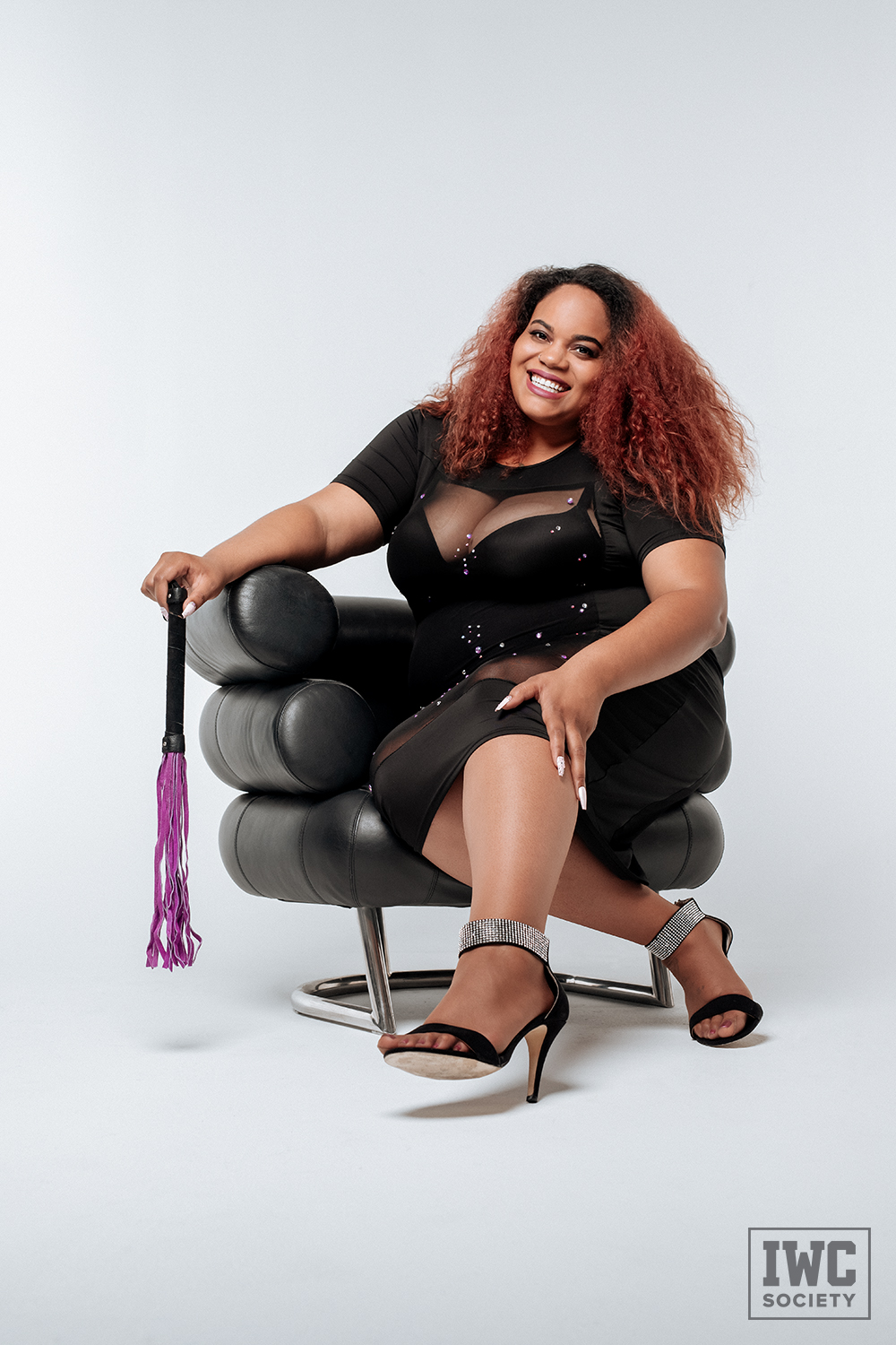black dominatrix Ms Charmness sitting on a black chair holding a purple flogger with a gorgeous smile