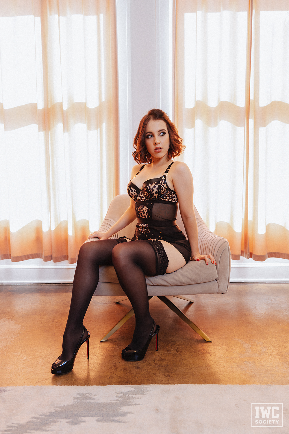 Financial Domme Princess Violette sitting on chair in front of windows in lingerie