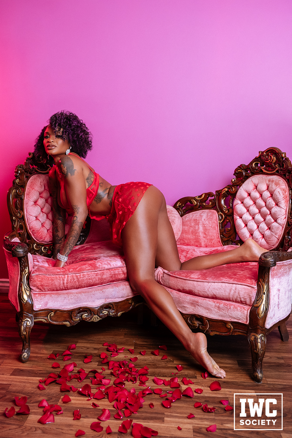 Ebony tattooed queen bending forward on pink sofa chairs