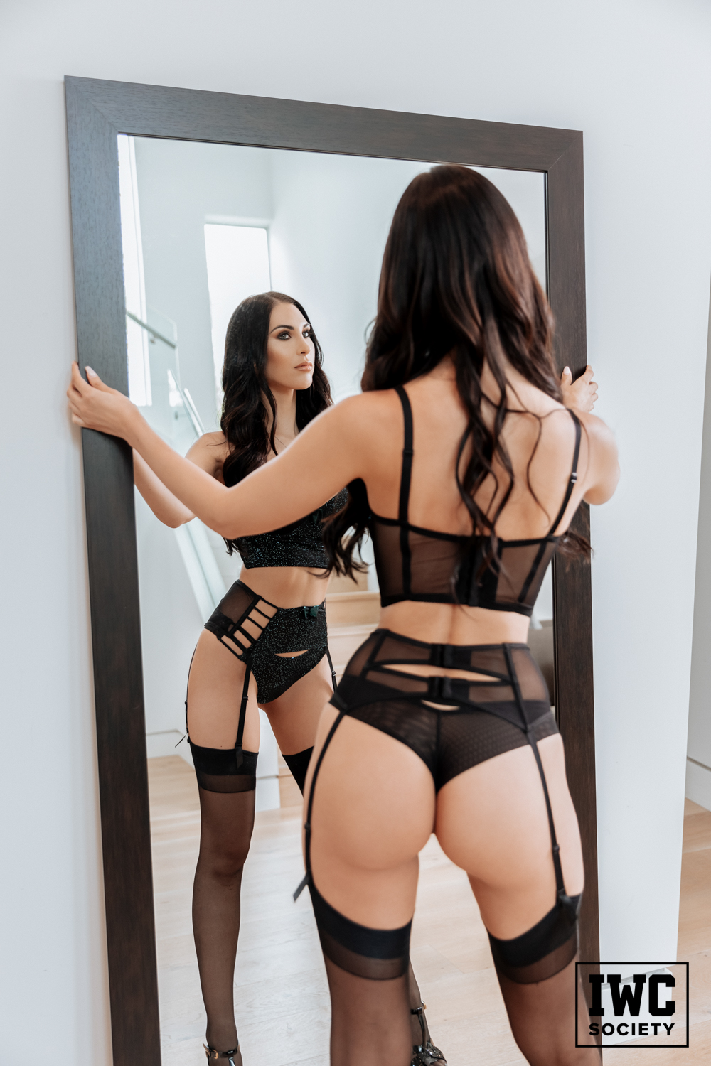 dominatrix in mesh lingerie with stockings in mirror