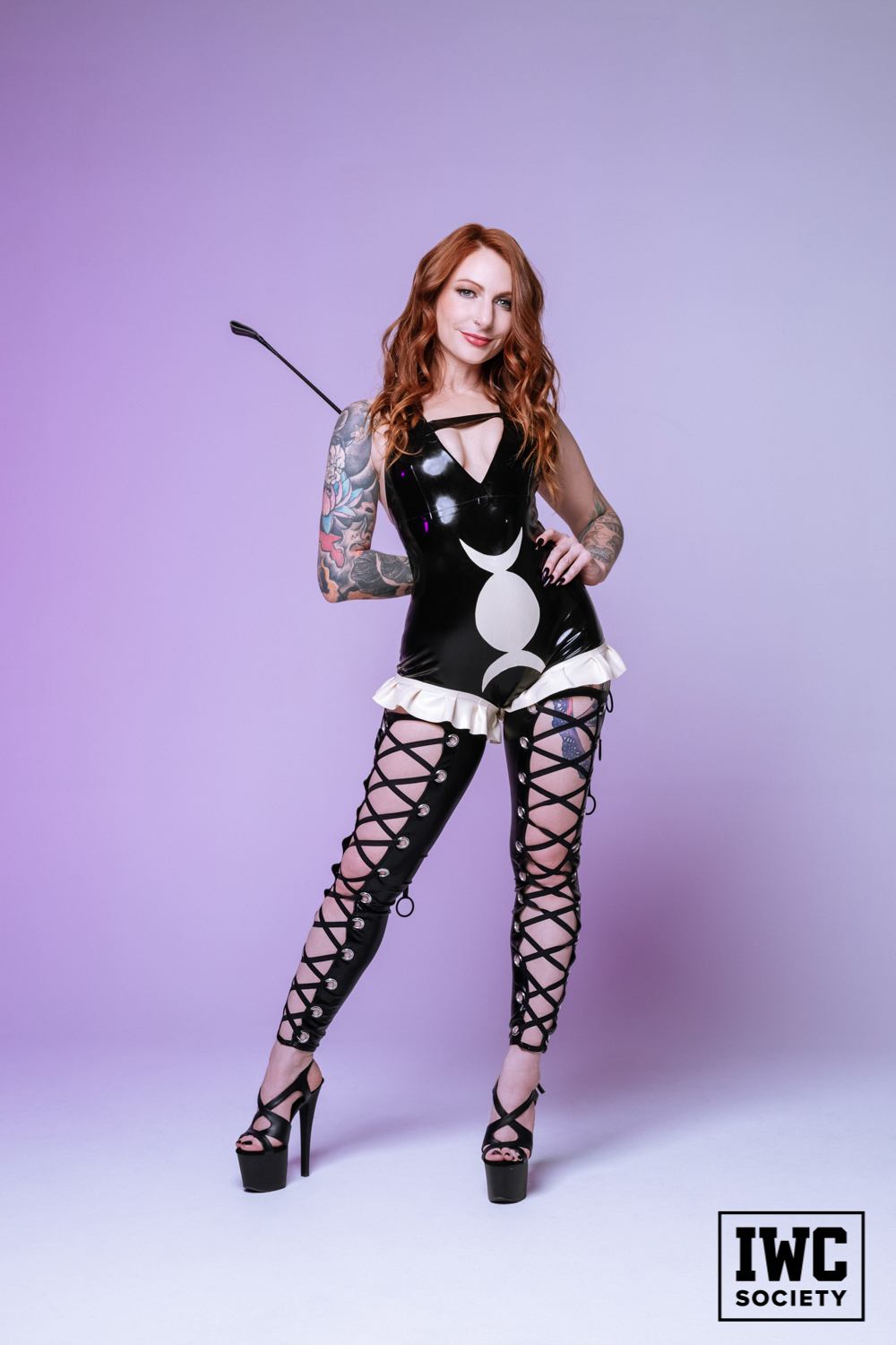 redhead femdom with tattoos in black latex and heels