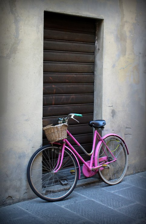 Bicicle with a Basket leaning against a wall in the streets of Florence