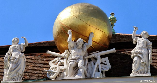A gilded globe supported by Atlas on the left side of the main building (Österreichische Nationalbibliothek) National Library, in Josefsplatz, Vienna