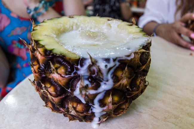 A piña colada served on a fresh pineapple.
