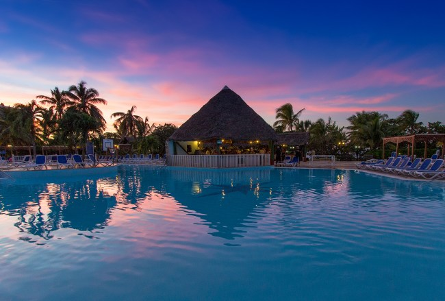 View of the main pool at sunset at the Breezes Bella Costa hotel and resort