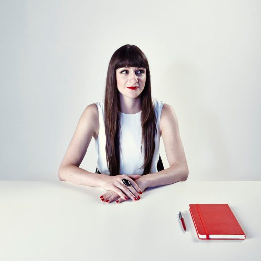 Woman with long straight brown hair and bangs wears a sleeveless white dress against a white background and white desk. A red notebook and pen is on the desk in front of her.