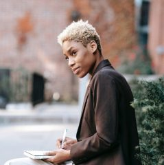 thoughtful black entrepreneur writing notes in notebook