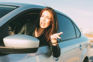 Beautiful brunette long hair angry young asian woman driving and screaming in car
