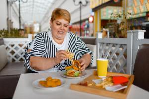 Fat woman eating high calorie food in mall