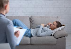 Depressed young woman consulting psychologist, lying on couch and crying