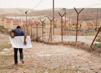 Palesztin fiú egy illegális izraeli település kerítésének túloldalán, Ciszjordániában - fotó: Garry Walsh / Trócaire / Creative Commons
