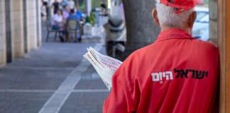 Jiszrael Hajom újságot osztó férfi Jeruzsálemben - fotó: Shutterstock