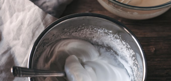 Eggs, Sugar, Milk, Flour Batter In A Glass Bowl And Whipped Eggs Whites In A Mixing Bowl On A Wooden Table