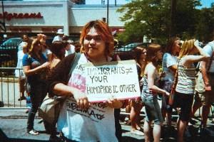 """プライドパレードで手書きのプラカードを持つマサキ。プラカードには """"IMMIGRANTS ≠ YOUR HOMOPHOBIC OTHER"""" とある。"""