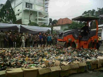 Sebuah buldoser menghancurkan ribuan botol minuman keras di lapangan Cikapundung, Rabu (12/3). Miras tersebut hasil razia yang dilakukan Polrestabes Bandung demi menjaga kondusifitas jelang Pemilu 2014. (JABARTODAY/AVILA DWIPUTRA)