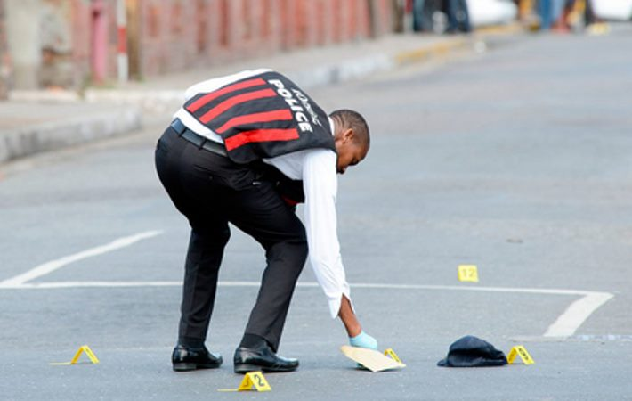A policeman places markers at a crime scene - Image via jamaica-gleaner.com
