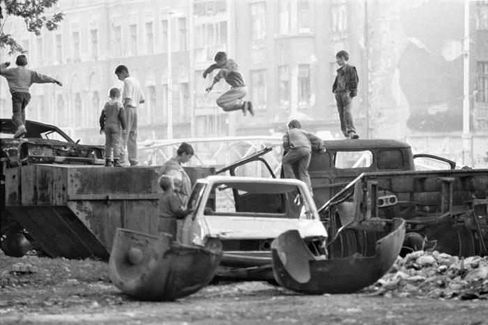Varios niños juegan entre coches y caminonetas destrozadas_Sarajevo 1993