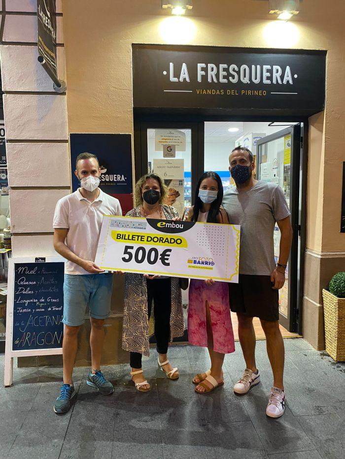 La Fresquera de Jaca entrega el billete dorado de 500€ de la campaña de verano de Acomseja. En la imagen, la presidenta de Acomseja, Marian Bandrés, y Javier Gállego (La Fresquera), junto a los ganadores. (FOTO: Acomseja)