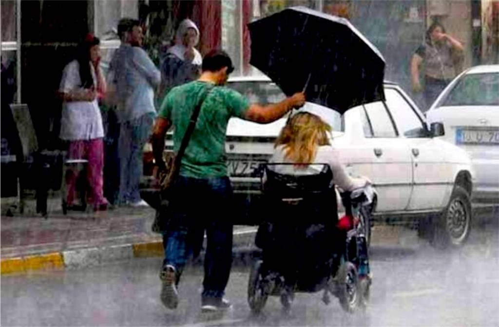 person holding umbrella for someone in wheelchair in rain