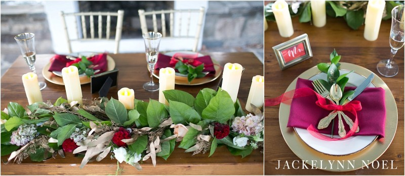 Photo of the head table. Gold place settings, candles, and a floral garland.