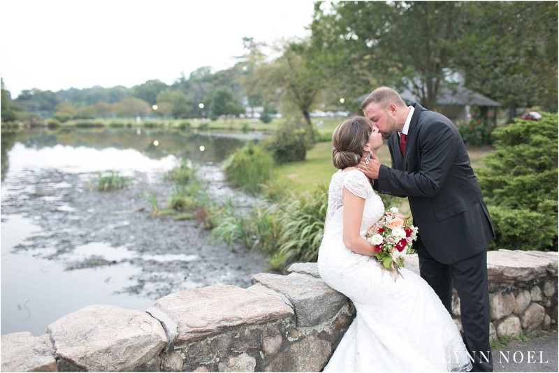 Photo of Matt kissing Leila with the twinkling lake in the background.
