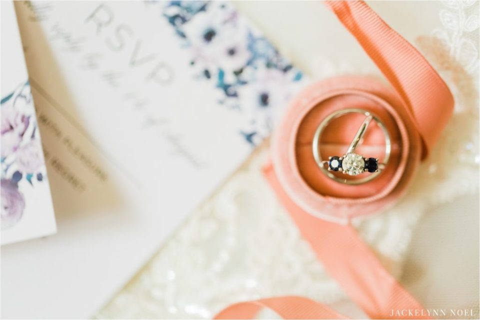 Close up of Lisa and Dan's wedding bands in a pink ring box with ribbon and lace