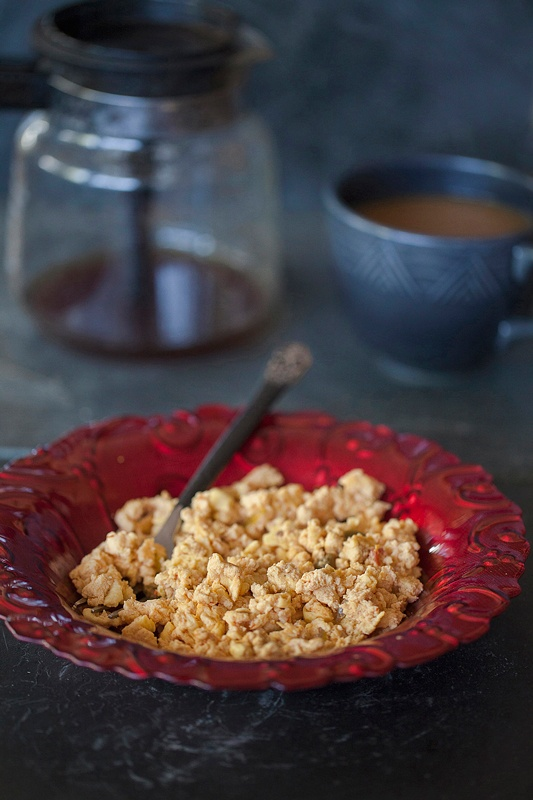 Scrambled Eggs With Gorgonzola & Salsa served in a red glass bowl with coffee