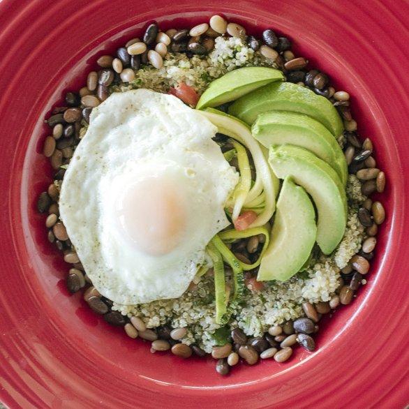 tepary beans, egg, avocado, quinoa, zucchini, in a red fiesta platter